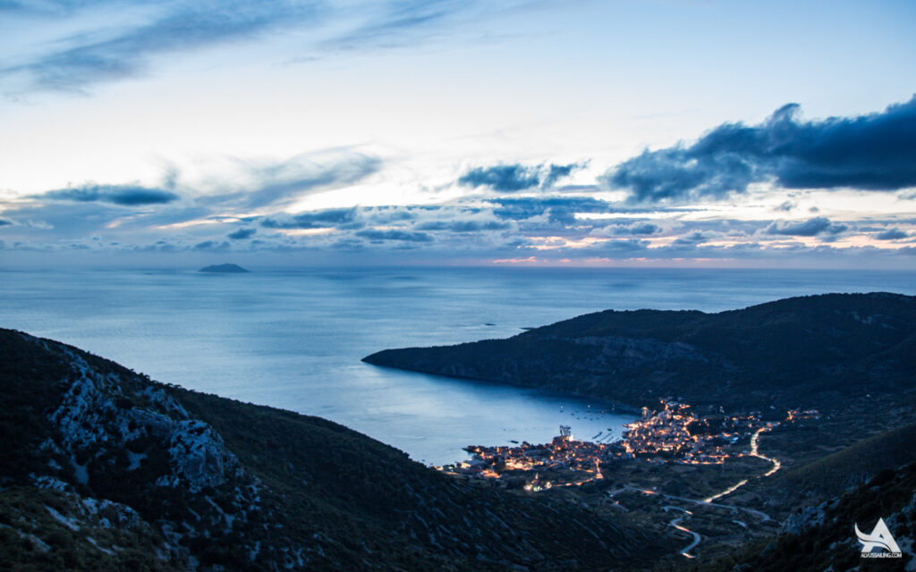 Komiza on Vis island in the distance with October clouds over the bay. View form the Hum top.