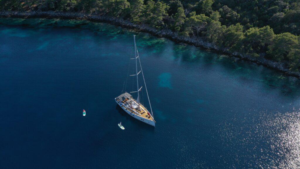 drone shot sailing monohull at anchor with sup paddleboards